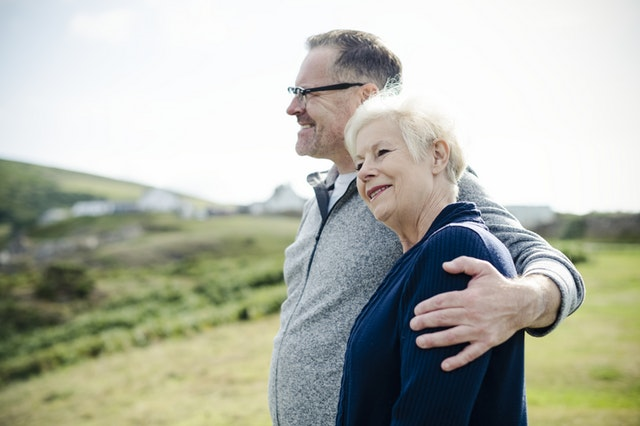 elder couple standing on hill